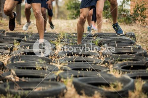 Low section of people receiving tire obstacle course training