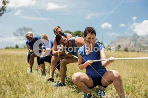 People playing tug of war during obstacle training course