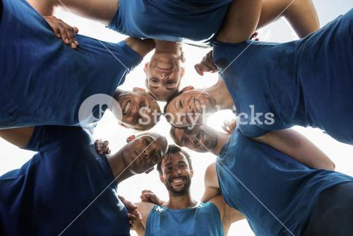 Fit people standing together and forming a hurdle