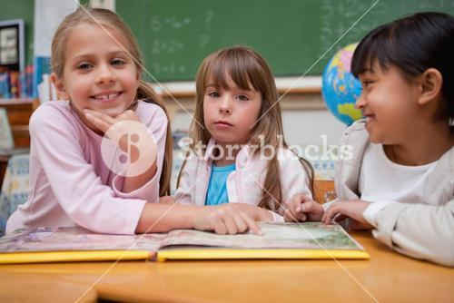 Schoolgirls reading a fairy tale to their classmate