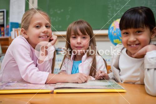 Happy schoolgirls reading a fairy tale to their classmate