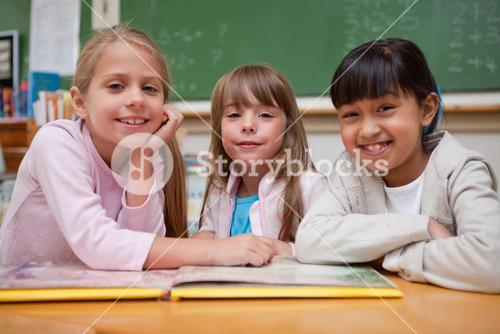 Smiling schoolgirls reading a fairy tale to their classmate
