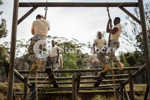Military soldiers training rope climbing