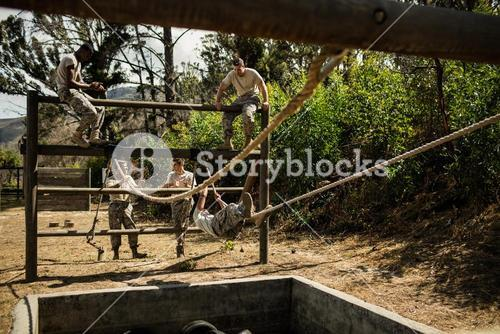 Young military soldiers practising rope climbing during obstacle course