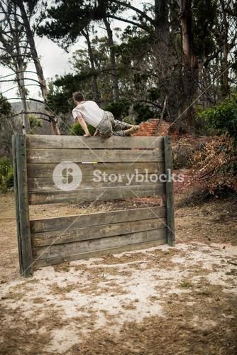 Soldier climbing wooden wall in boot camp