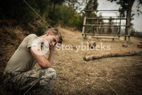 Tired soldier with hand on head sitting