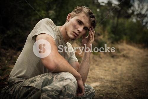 Tired soldier with hand on head sitting in boot camp