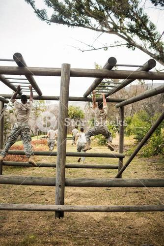 Soldiers climbing monkey bars