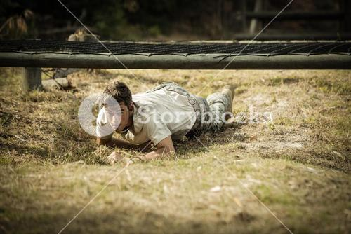 Soldier crawling under the net during obstacle course