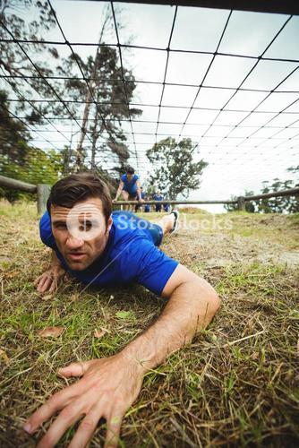 Fit man crawling under the net during obstacle course