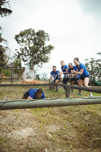 Fit man crawling under the net during obstacle course while fit people cheering