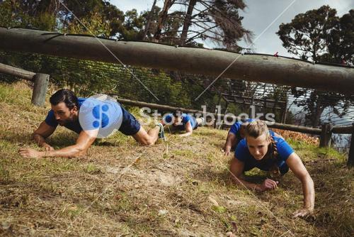 Fit people crawling under the net during obstacle course