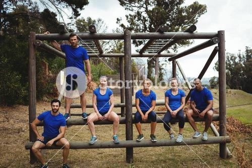 Fit people sitting on the obstacle couse in bootcamp