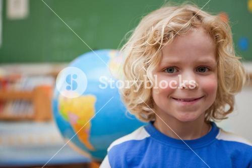 Schoolboy posing in front of a globe
