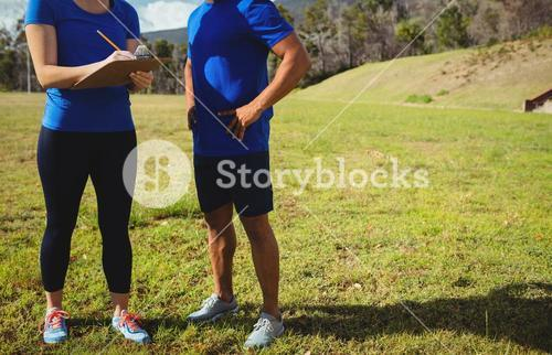 Female trainer instructing a man in bootcamp