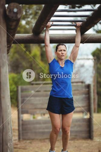 Fit woman climbing monkey bars