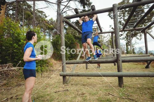 Fit people climbing monkey bars