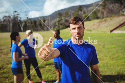 Fit man showing thumbs up in bootcamp