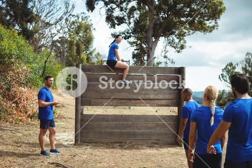Fit woman sitting over wooden wall during obstacle course