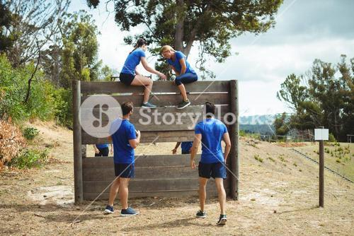 Female trainer assisting fit woman to climb over wooden wall during obstacle course