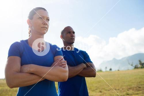 Female trainer and male trainer standing with arms crossed