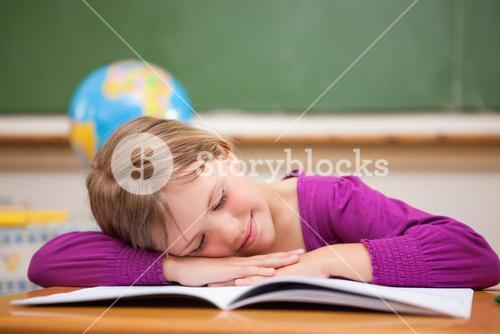 Schoolgirl sleeping on her desk