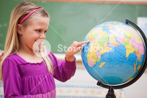 Cute schoolgirl pointing at a country