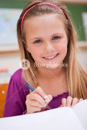 Portrait of a little schoolgirl writing