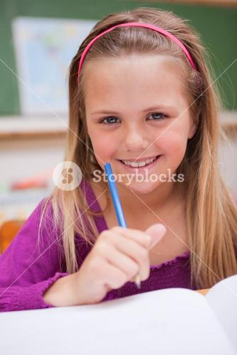 Portrait of a little schoolgirl writing on a book