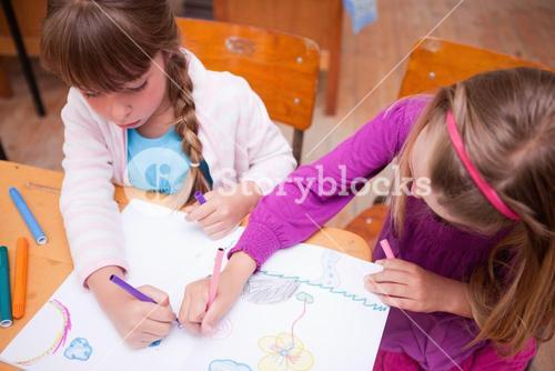 Schoolgirls drawing in a coloring book