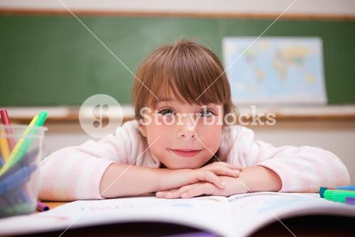 Smiling schoolgirl leaning on a desk