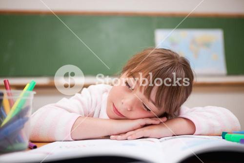 Schoolgirl sleeping on a desk