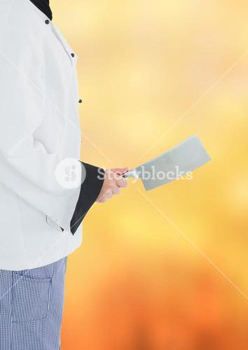 Chef with cleaver against blurry orange background