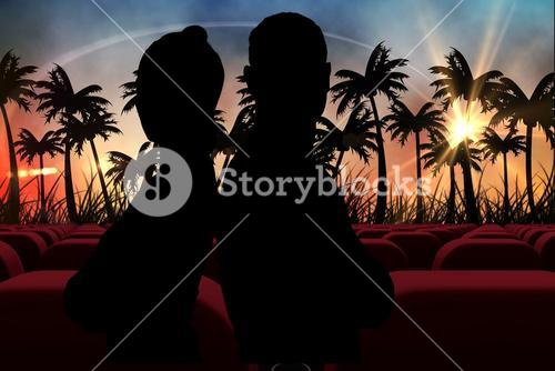 Silhouetts of  couple against 3d  cinema seats facing sunset view with palms