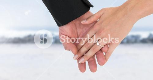 Wedding couple holding hands by sea
