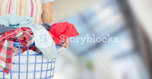 Woman in apron with laundry against blurry window