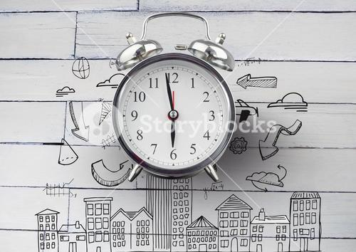 Clock in front of diagrams and buildings drawings against wood