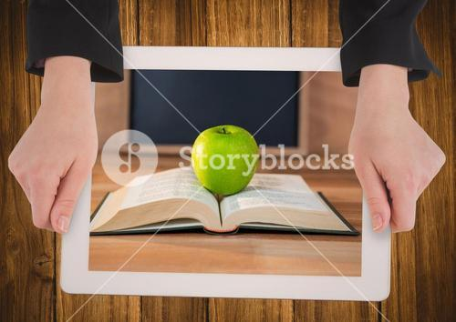 Hands with tablet on table showing book with green apple