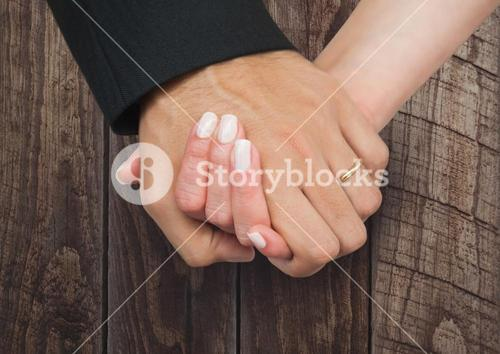 Wedding couple holding hands against wood