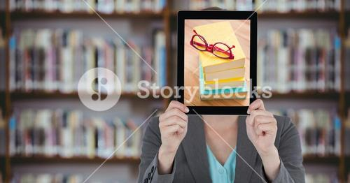 Business woman with tablet over her face with piles of books while standing at  library