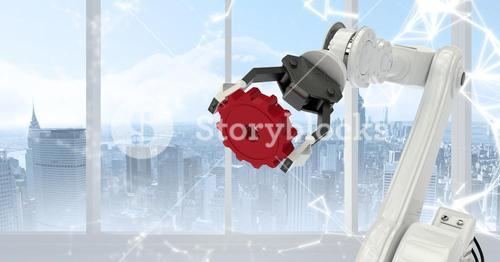 White robot claw holding red cog against white interface and window with skyline
