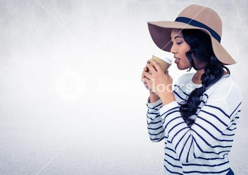 Woman with hat drinking from coffee cup against white wall