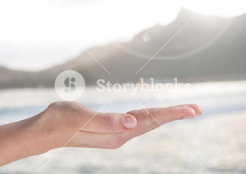 Open palm hand in front of ocean and mountains