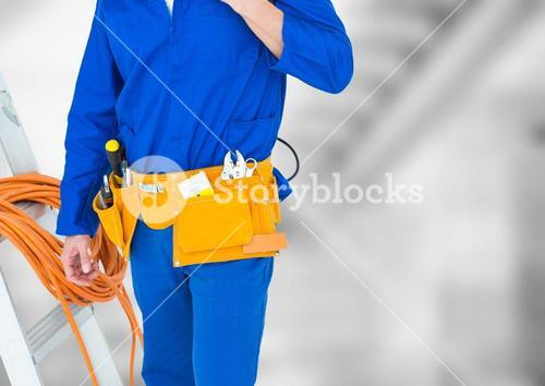 Handyman lower body with ladder against blurry grey stairs