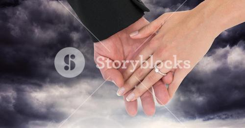 Wedding couple holding hands in front of dark clouds