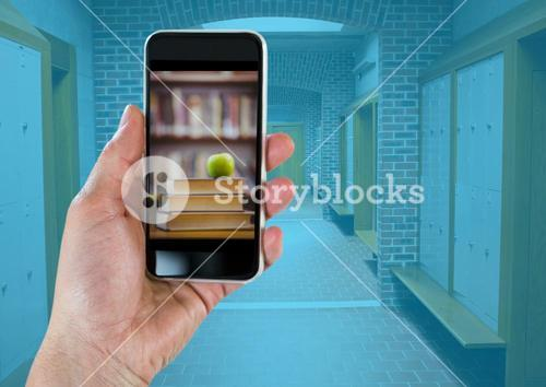 Hand with phone showing book pile with green apple against hallway with blue overlay