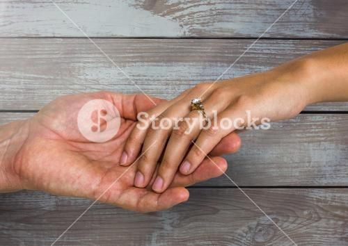 Wedding engaged couple holding hands against wood