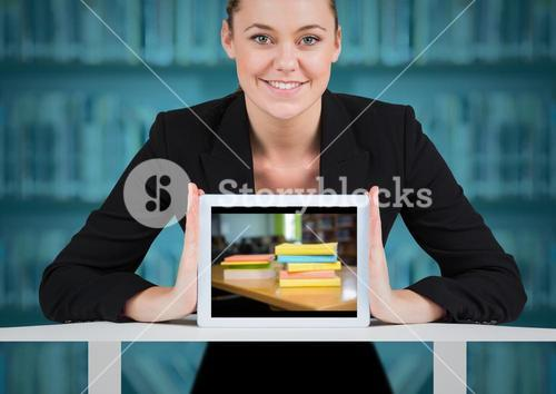 Business woman with tablet showing book pile against blurry bookshelf with blue overlay