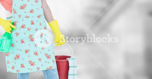 Woman lower body in apron with bucket against blurry grey background