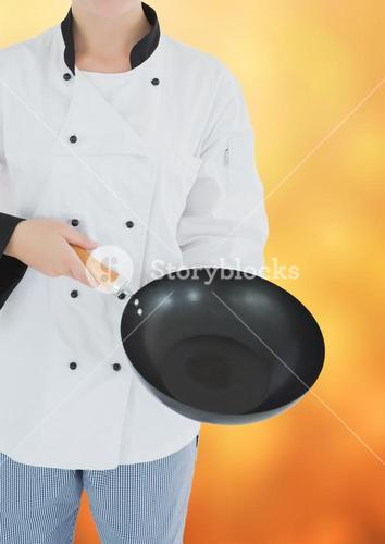 Chef with wok against blurry yellow background